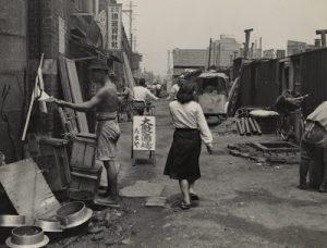 A prostitute walks down a street in postwar Tokyo slum