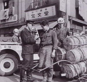 A police officer confiscates goods from an illegal ramen vendor in 1949.
