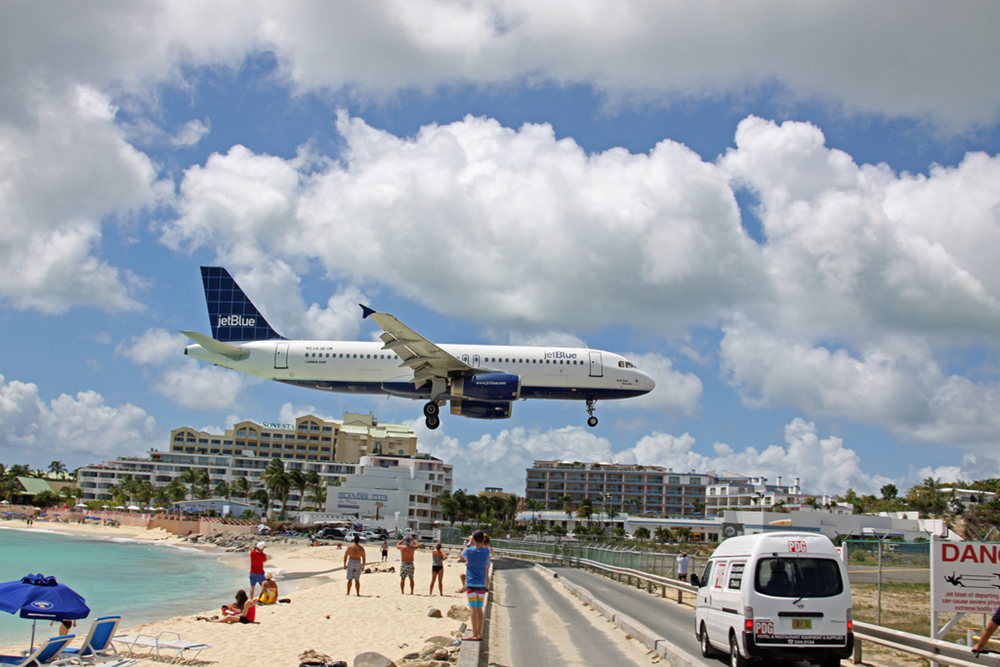 An airplane flying very low to the ground, just above a beach full of onlookers, as it comes in for a landing.