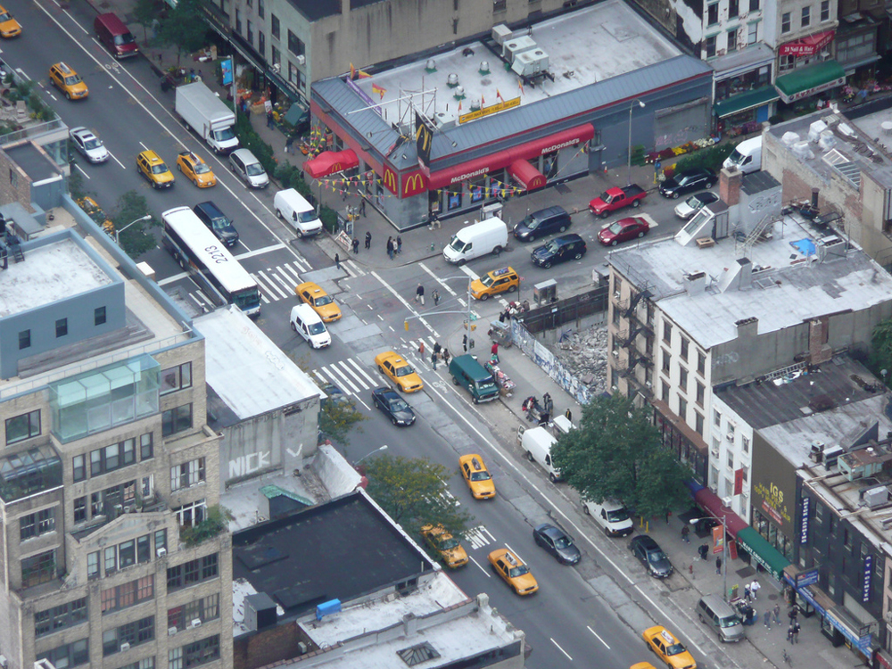 A busy traffic intersection in New York showing vehicles moving on the road.