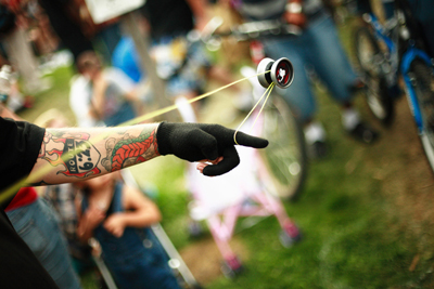 The figure shows the left arm of a man with tattoo imprints and wearing a glove. He is circulating a yo-yo toy, which is in mid air and connected by the string to his hand. Some people are standing in the background watching the yo-yo trick.