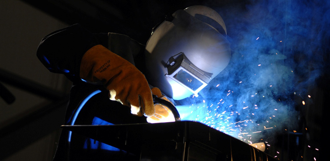 Photograph of a welder wearing protective gloves and helmet, engaged in the task of welding.