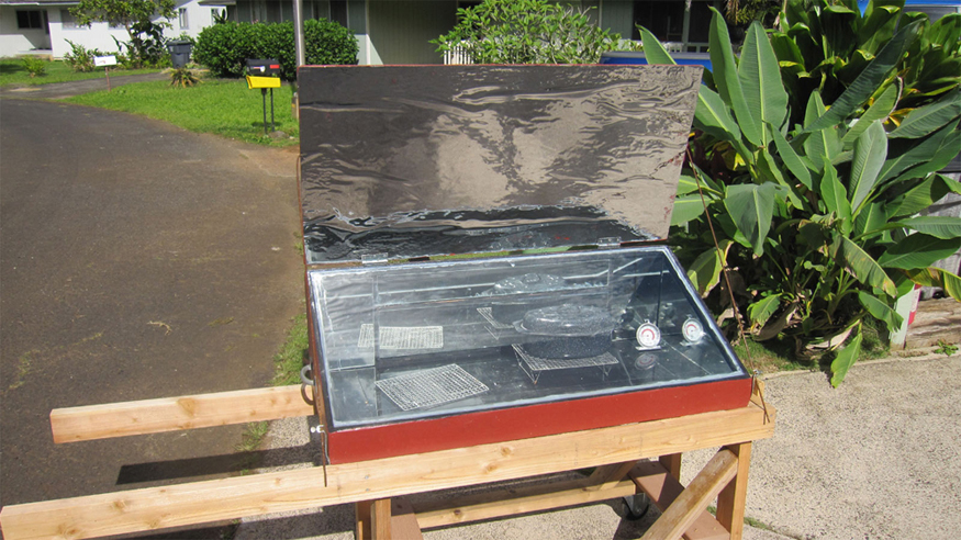A solar cooker is shown. There is a pot of food inside the solar cooker. The sunlight is incident on the solar cooker and the food is being cooked.