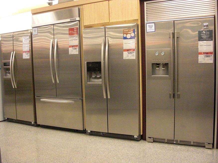 Photograph of various expensive refrigerators displayed in a home appliance store.