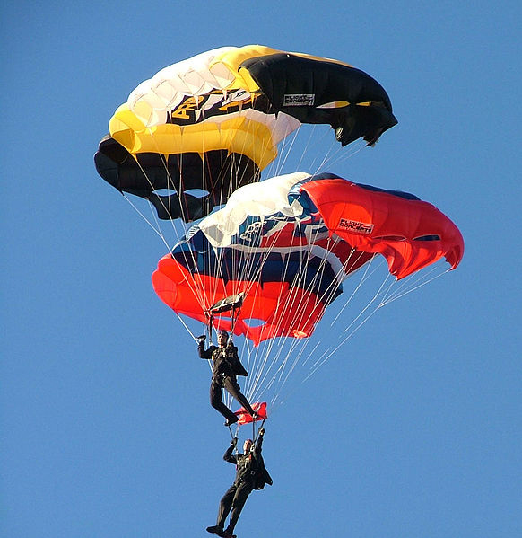 The figure shows two skydivers midway through the air, with both with open having their parachutes open.