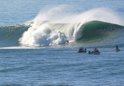 There is a high tidal wave of about 10 feet high in a sea. Three boats carrying three four persons each are ahead of the wave, which is coming toward them.