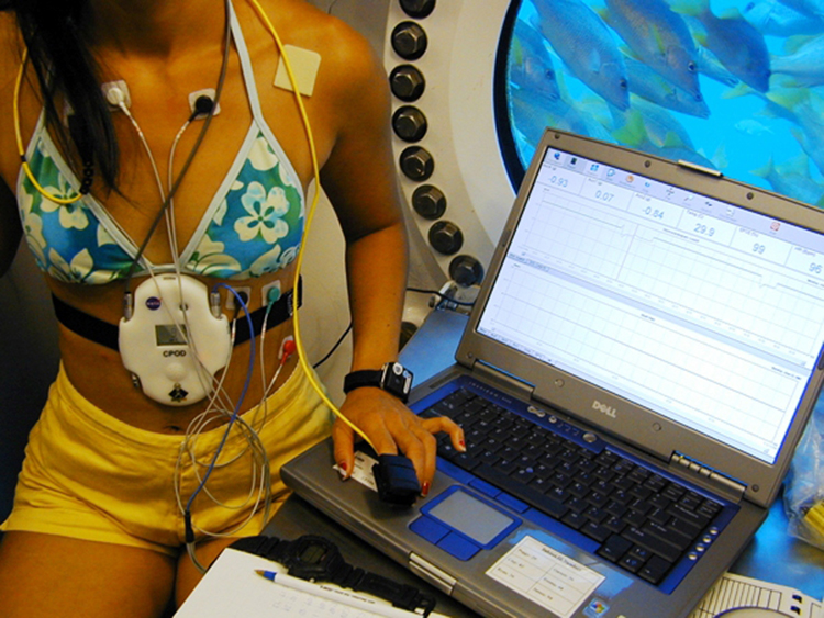 Photograph of a NASA scientist in an underwater habitat recording her vital signs using a portable device and a laptop computer.