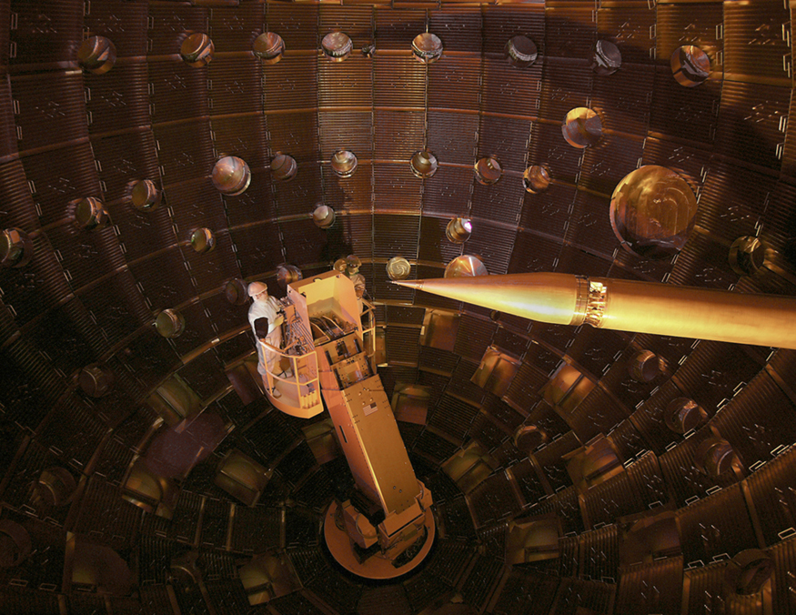 The image shows the inner part of a large shell-like structure where two persons are standing on a boom. The image also shows a sharp pencil shaped structure that serves to hold the fuel pellet at the focus point of all the lasers.