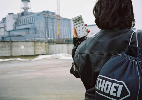A person holding a hand held radiation detector near the Chernobyl reactor.