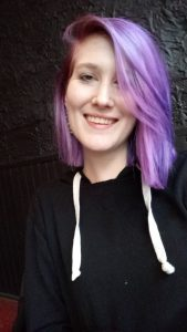 Image of Jamie Peterson. Caucasian woman with lavender-colored, shoulder-length hair and wearing a black sweater.