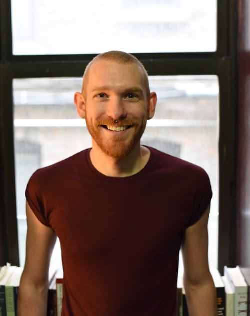 Image of poet Stephen Mills. Caucasian male with a close-shaved head, beard, nose ring and wearing a dark red t-shirt.