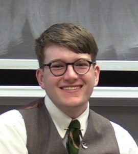 Image of Ben Guard. Caucasian male with brown hair and glasses, wearing white button down shirt, green tie, and brown vest.