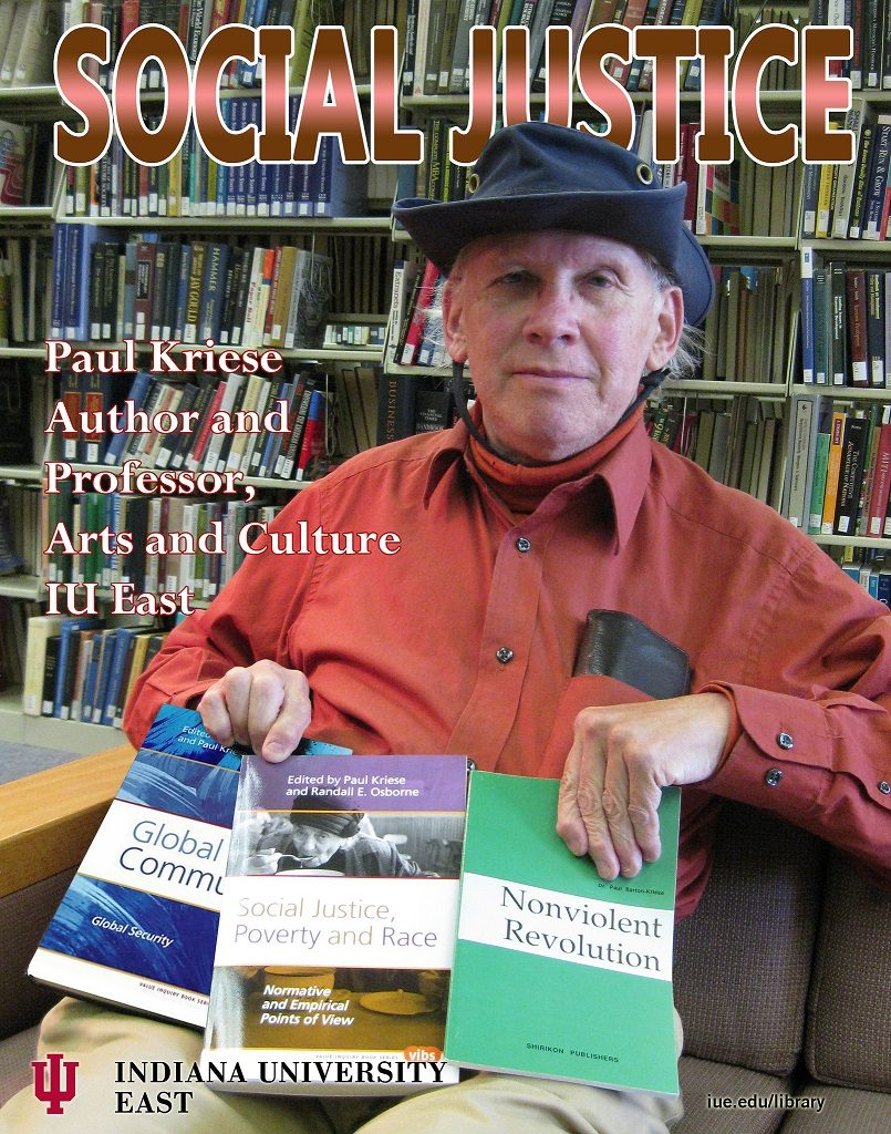Image of Dr. Paul Kriese. Caucasion male, wearing a hat and a red shirt, sitting on a couch in front of the library bookshelves, and holding three of his books, titled Global Communities; Social Justice, Poverty, and Race; and Nonviolent Revolution.