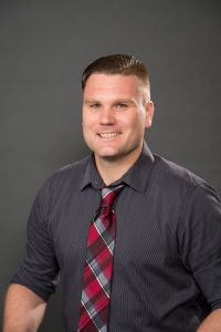 Work photo of Josh Tolbert. Caucasian male wearing gray button down shirt and red and gray plaid tie.
