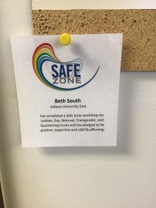 Image of Safe Zone door sticker. Sticker says Safe Zone, participants name, and the disclosure that the participant has completed a Safe Zone workshop and has pledged to be positive, supportive, and LGBTQ-affirming.