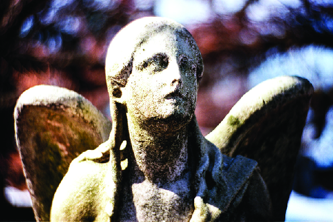 A photograph is shown of an angel statue. While some details of the statue, including facial features, are present, effects of weathering appear to be diminishing these features.