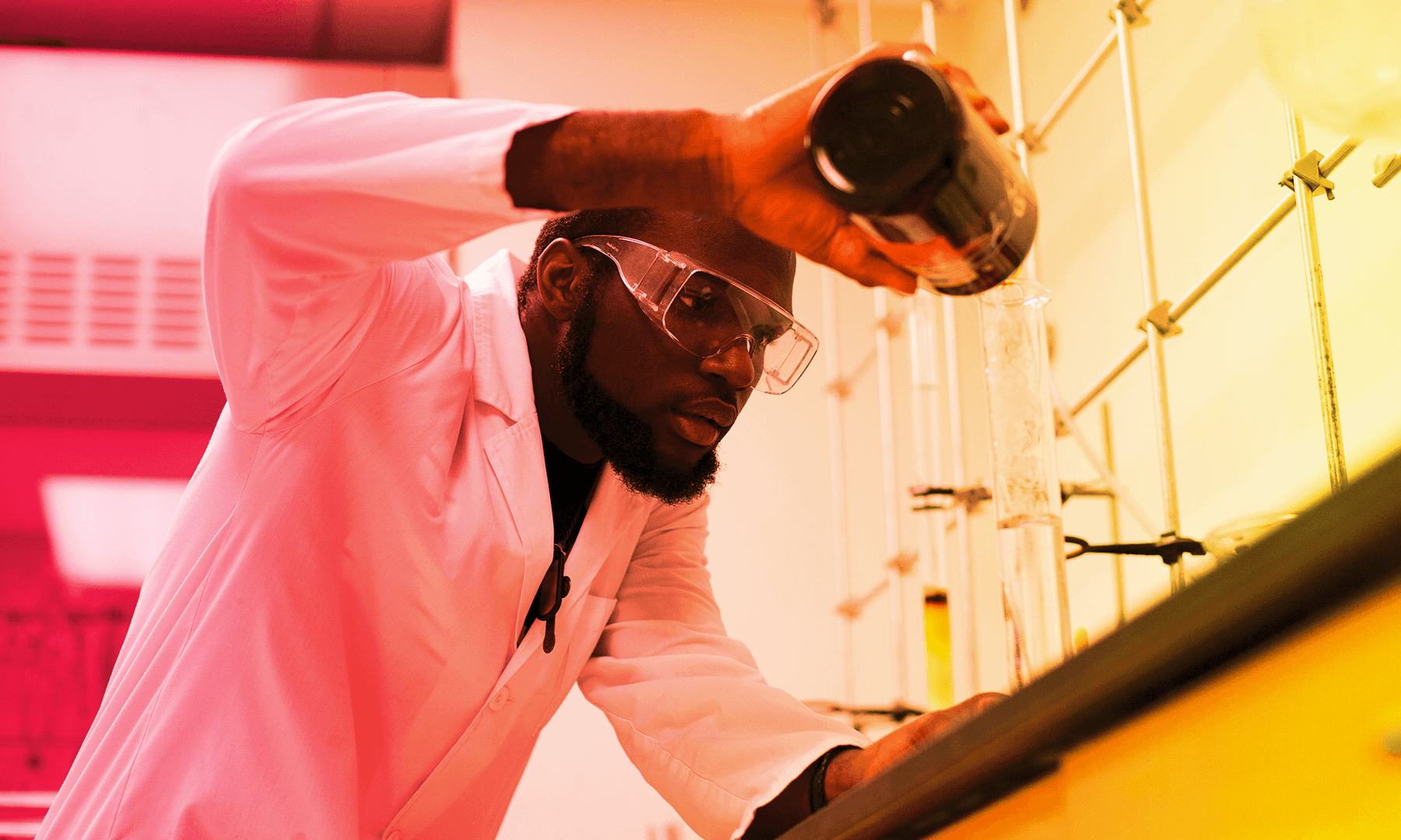 african american male student wearing lab coat and goggles pouring from a dark colored bottle into a test tube in a science lab
